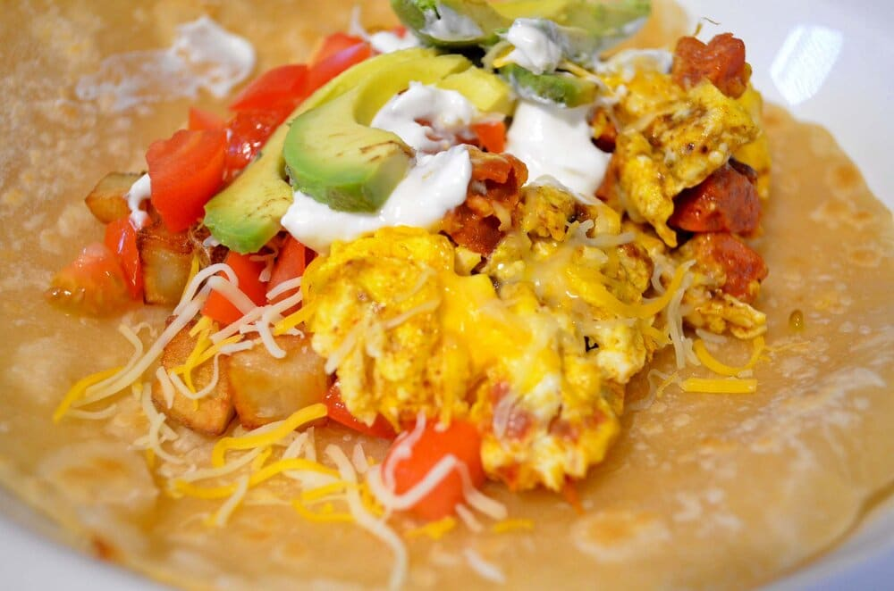 Malaysian curried chorizo eggs with fried potatoes, tomatoes, sour cream, avocado & shredded cheese